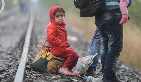 Syrian girl sitting on tracks near temporary refugee camp.