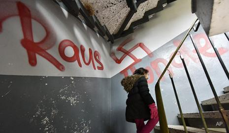 Anti-immigrant graffiti in apartment building stairwell (AP photo)